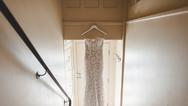 Bride's wedding dress hanging from the staircase
